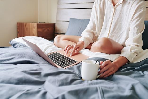 ベッドに座って、コーヒーを飲み、ラップトップで目を覚ます、電子メールやメッセージに答える若い女性のトリミングされた画像