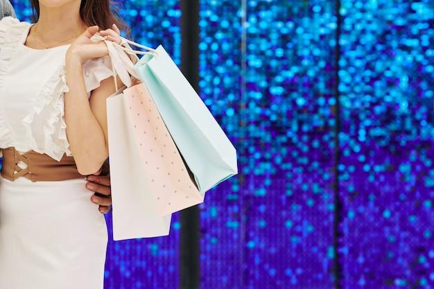 たくさんの買い物袋があるきらめく壁に立っている若い女性のトリミングされた画像