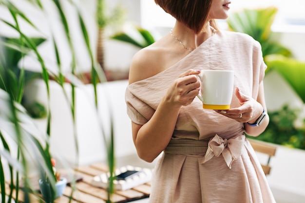 ホットコーヒーまたは紅茶の大きなマグカップで立っている若い女性のトリミングされた画像