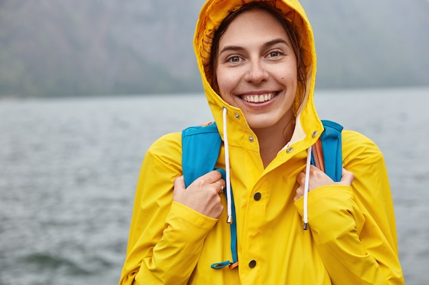 L'immagine ritagliata di una donna europea ottimista indossa un cappuccio giallo, porta uno zaino, ha un ampio sorriso