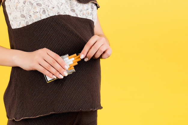 Cropped image of a pack of cigarettes at yellow background. bad habbit of a pregnant woman in brown pajamas. careless mother.