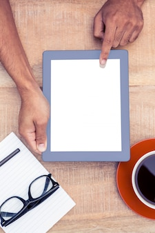 Cropped image of person using on digital tablet by coffee and document on table