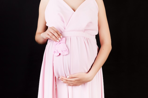 Cropped image of pink socks for a baby girl in pregnant woman's hands against her belly at black background. happy pregnancy. copy space