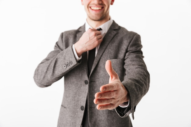 Cropped image of pleased business man in jacket holding his tie and giving hand to handshake over white wall
