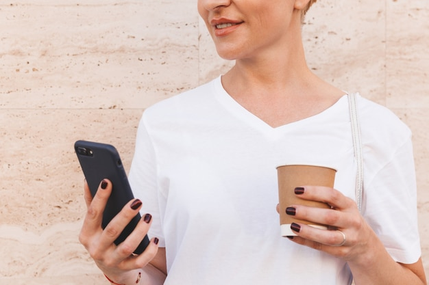 Cropped image of pleased european woman wearing white t-shirt using black mobile phone, while standing against beige wall in street and drinking coffee from paper cup