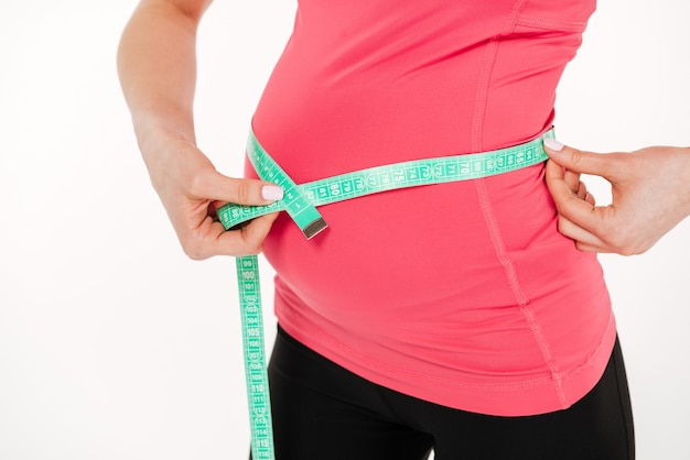 Cropped image of pregnant fitness woman measurement her tummy