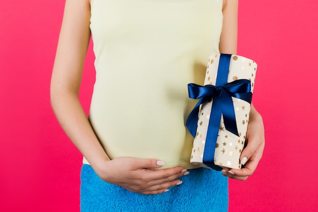 Cropped image of pregnant woman in colorful home clothing holding a gift box and touching her belly at pink background. expecting a baby boy. copy space