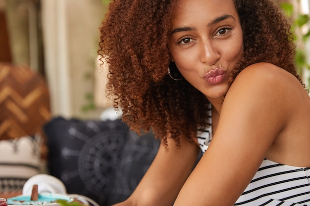 L'immagine ritagliata di una ragazza dalla pelle piuttosto scura ha un taglio di capelli afro