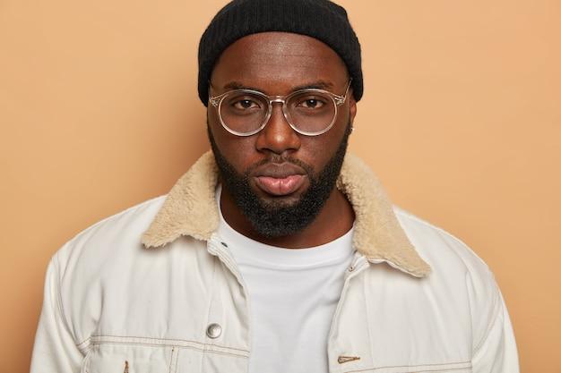 Immagine ritagliata di un uomo di colore serio con labbra carnose, barba folta, indossa occhiali da vista