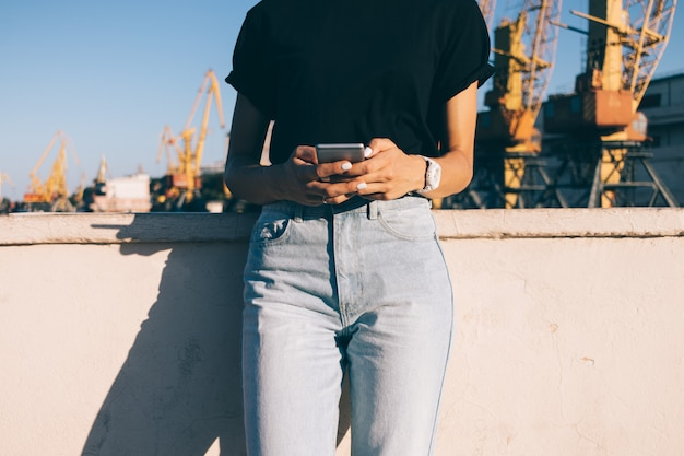 Cropped image of a slender girl in jeans with a phone