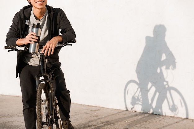 Cropped image smiling asian man riding a bicycle outdoors, drinking water from a bottle