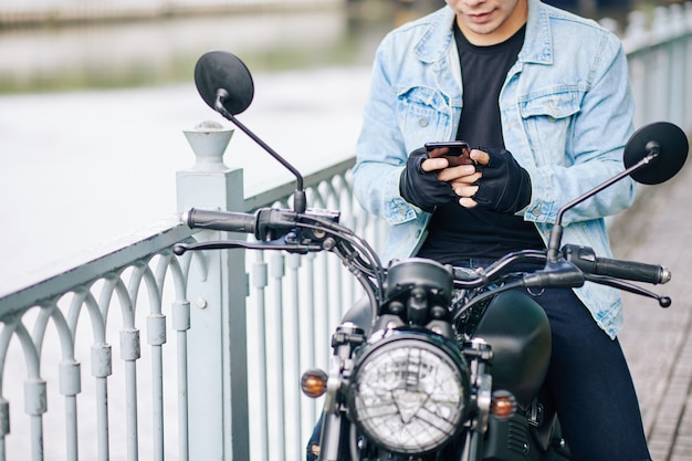 Cropped image of smiling biker in denim jacket and fingerless gloves sitting on motorcycle and texting friend or girlfriend