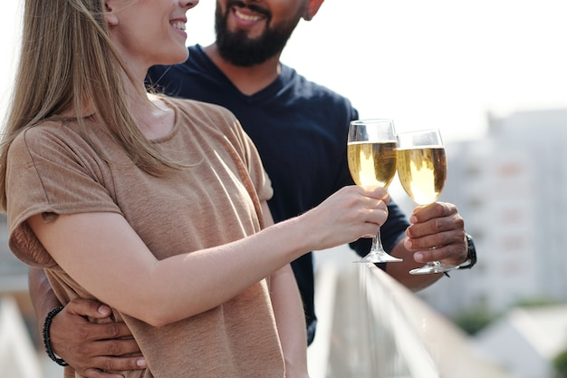Cropped image of smiling hugging young couple enjoying drinking champagne on rooftop