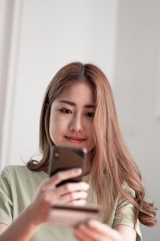 Cropped image of smiling millennial woman holding smartphone and banking credit card, involved in online mobile shopping at home, happy female shopper purchasing goods or services in internet store.