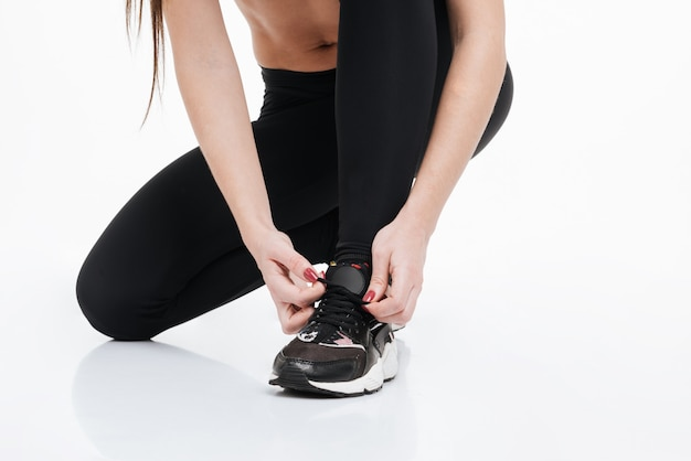 Cropped image of a sports female sitting and tying shoelace isolated