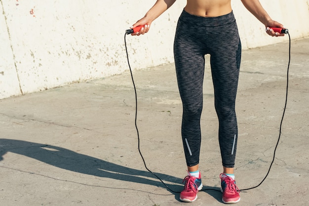 Cropped image of sports girl in sweat pants and sneakers which jumping rope in the morning sun
