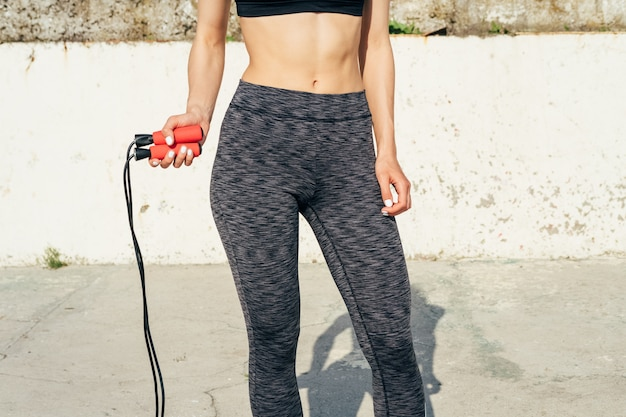 Cropped image of sports girl with a skipping rope in her hands