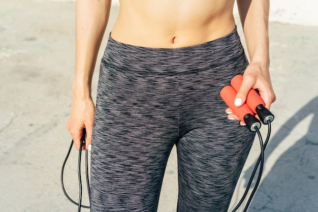 Cropped image of sports woman with a skipping rope in her hands