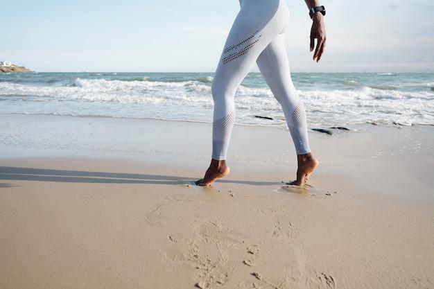 Cropped image of sportswoman in white leggings walking on tiptoes on sandy beach