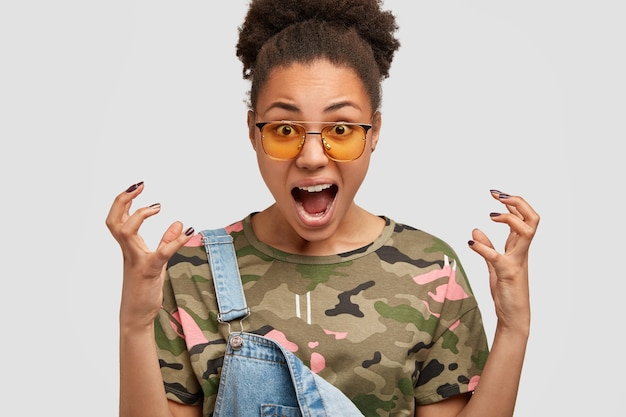 Cropped image of stressful annoyed black woman keeps hands in irritated gesture