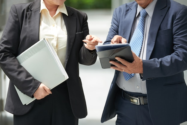 Cropped image of successful business partners pointing at tablet computer when discussing details of contract