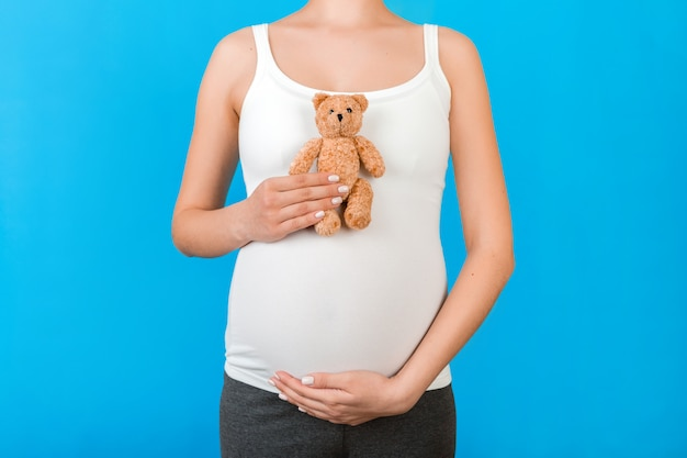 Cropped image of teddy bear in hand against pregnant woman's belly in home clothing at blue background. waiting for a childbirth.