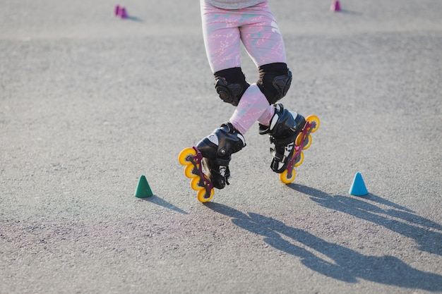 Cropped image of teenager wears roller skates outdoor, rollerblades across chips, has active holidays
