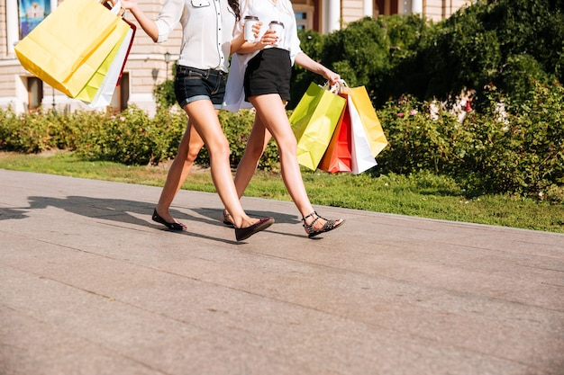 Cropped image of a two women walking along street with shopping bags and coffee cups