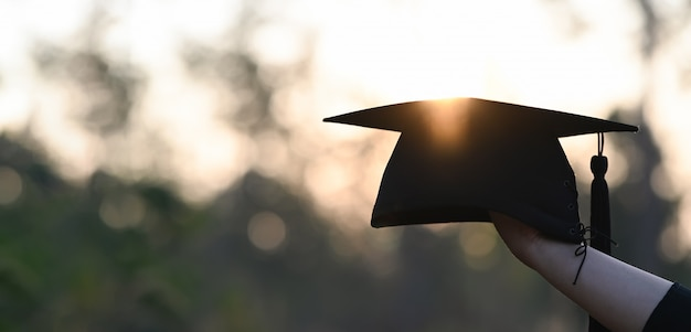 Cropped image of university student hand holding a graduation hat in hand over outdoors with sunset as background.
