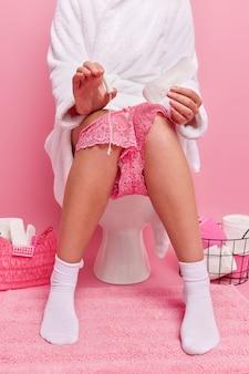 L'immagine ritagliata di una persona sconosciuta in morbido accappatoio bianco indossa mutandine di pizzo sulle gambe tiene un tampone pulito e un assorbente per le mestruazioni isolato sul muro rosa