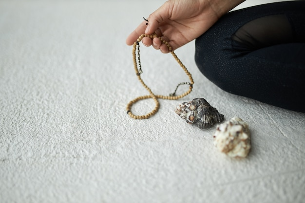 Cropped image of unrecognizable woman holding mala beads for prayer or meditation to keep track while chanting or repeating mantra, sitting on floor.