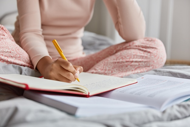 Cropped image of unrecognizable woman in nightclothes, writes down information in notepad, rewrites topic from textbook, poses at bed alone, has nice handwriting. close up shot, focus on writing