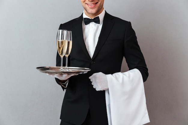 Cropped image of waiter holding glasses of champagne and towel.