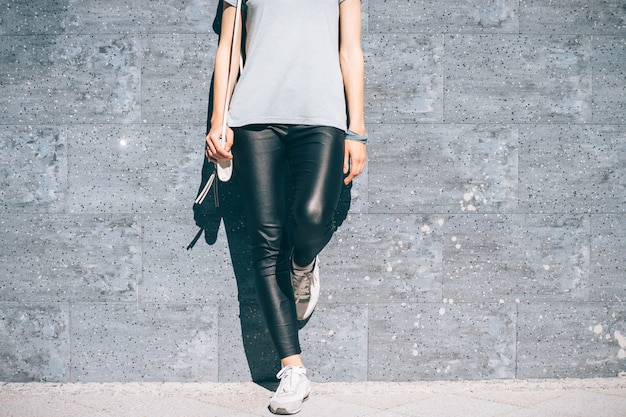 Cropped image of a woman in black pants and a blue t-shirt