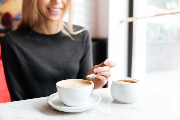 Cropped image of woman by the table with coffee