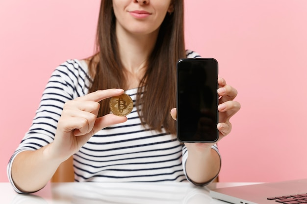 Cropped image of woman holding bitcoin metal coin of golden color future currency mobile phone with blank empty screen sit at desk isolated on pink background. achievement business career. copy space.