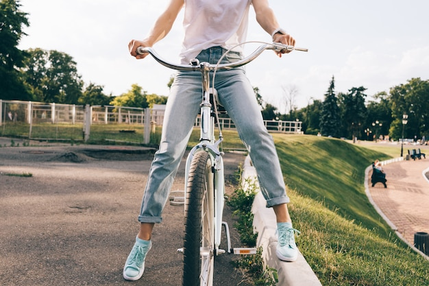 Cropped image of a woman in jeans and a t-shirt sitting on a city bicycle in a park