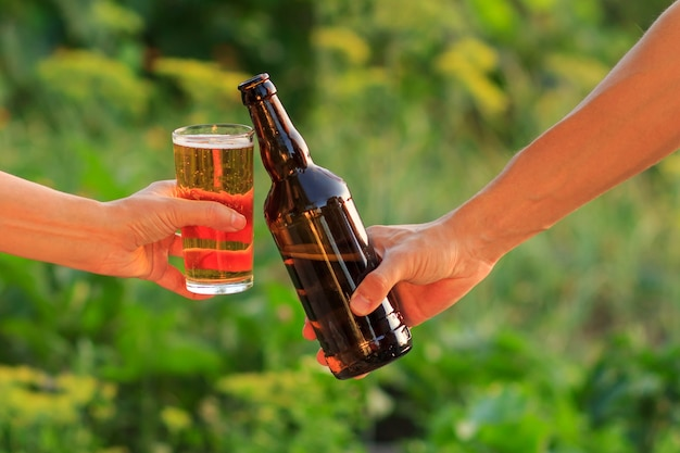 Cropped image of woman and man clanging glass of beer and bottle of beer together in natural green blurred background. woman clinked her glass against man with bottle