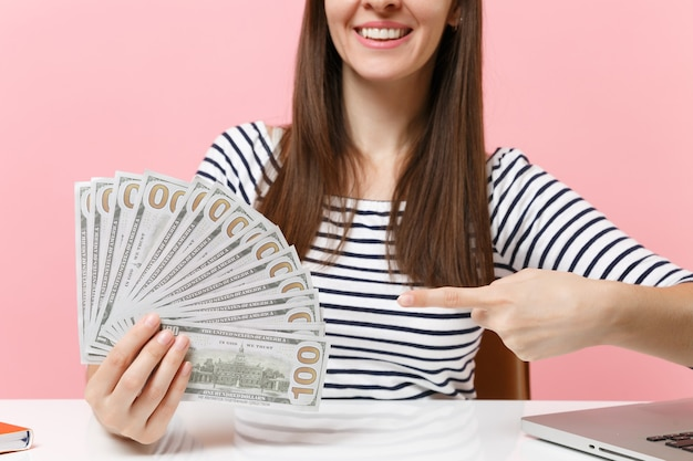 Immagine ritagliata di una donna che punta il dito indice sul fascio di un sacco di dollari in contanti e si siede alla scrivania