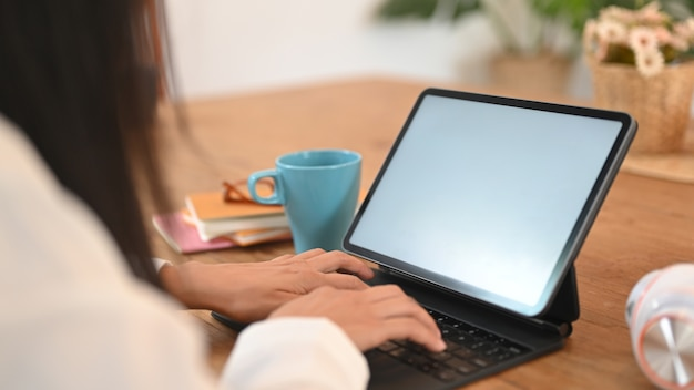 Cropped image of a woman's hands is using a white blank screen computer tablet on the wooden table.