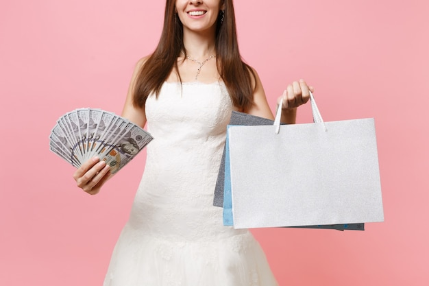Cropped image of woman in white dress holding bundle lots of dollars cash money, multi colored packages bags with purchases after shopping