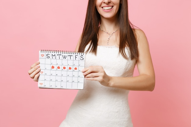 Cropped image of woman in white dress holding female periods calendar for checking menstruation days