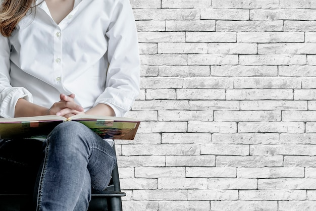 Cropped image of woman with book sitting on chair with old brick wall