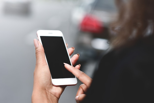 Cropped image of womans hands holding smart phone with blank copy space screen for text messages