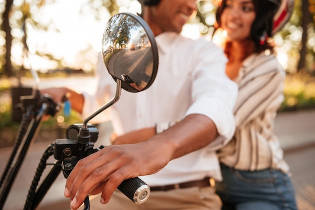 Cropped image of young african couple rides on modern motorbike in park and looking to each other. blur image