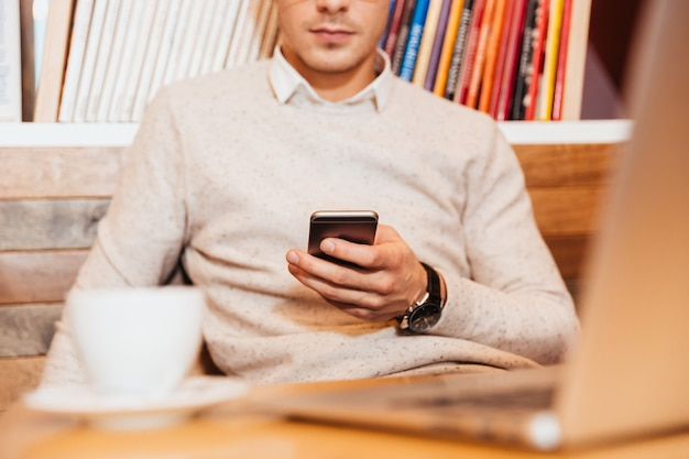 Cropped image of young attractive man sitting in cafe while using mobile phone and drinking coffee.