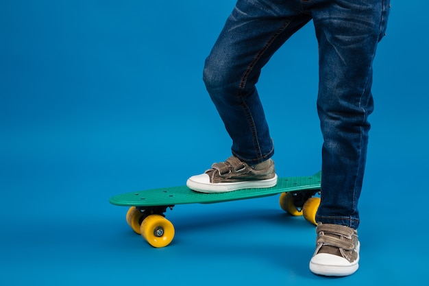 Cropped image of young boy comes on skateboard