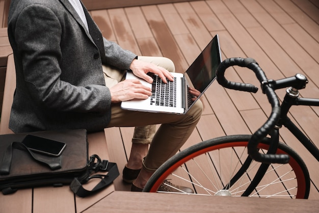 Cropped image of young businessman using laptop