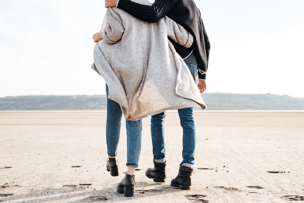 Cropped image of a young couple in casual clothes walking along seashore