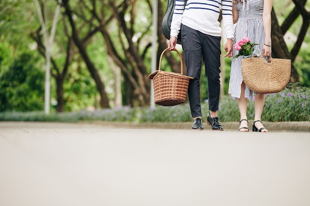 Cropped image of young couple with picnic baskets standing in city park